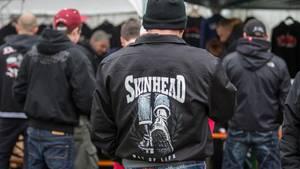 Publikum in schwarzen Jacken mit Skinhead-Logos