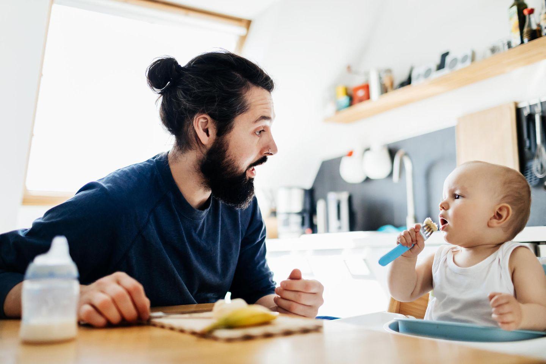 Vater guckt sein Kind beim Essen an