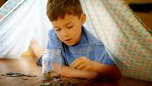 Kleiner Junge zählt Münzen