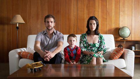 Eltern sitzen mit Sohn auf dem Sofa