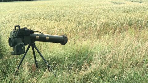 Neben dem Stamm einer Birke steht ein Raketenwerfer auf einem dreibeinigen Stativ im Gras am Feldrand