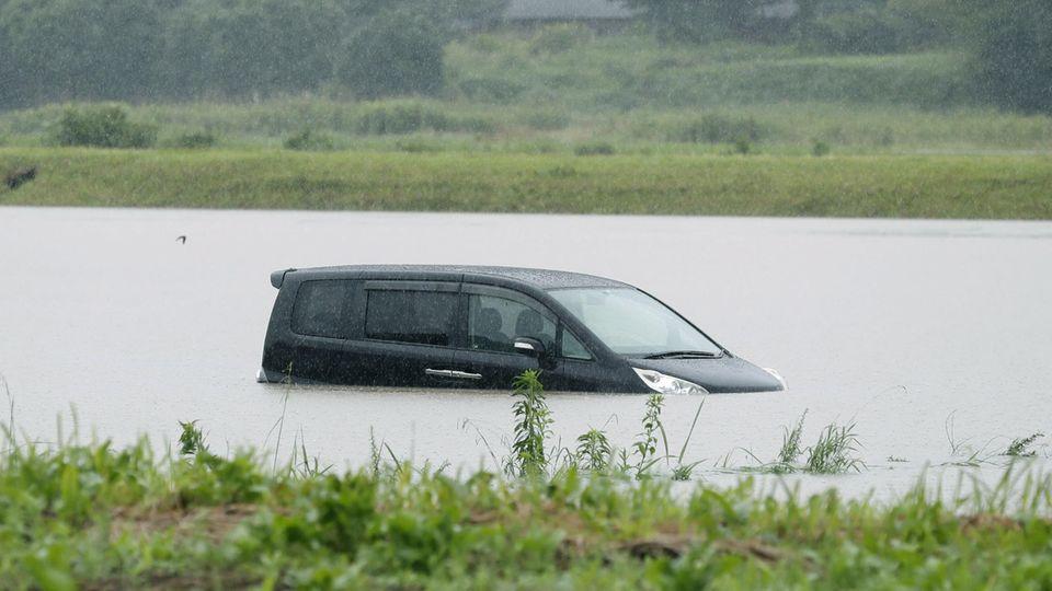Ein Auto versinkt in den Fluten der Regenfälle in Kagoshima, Japan