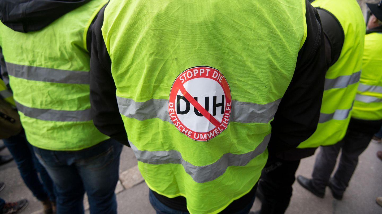 Menschen in Warnwesten protestieren gegen die deutsche Umwelthilfe