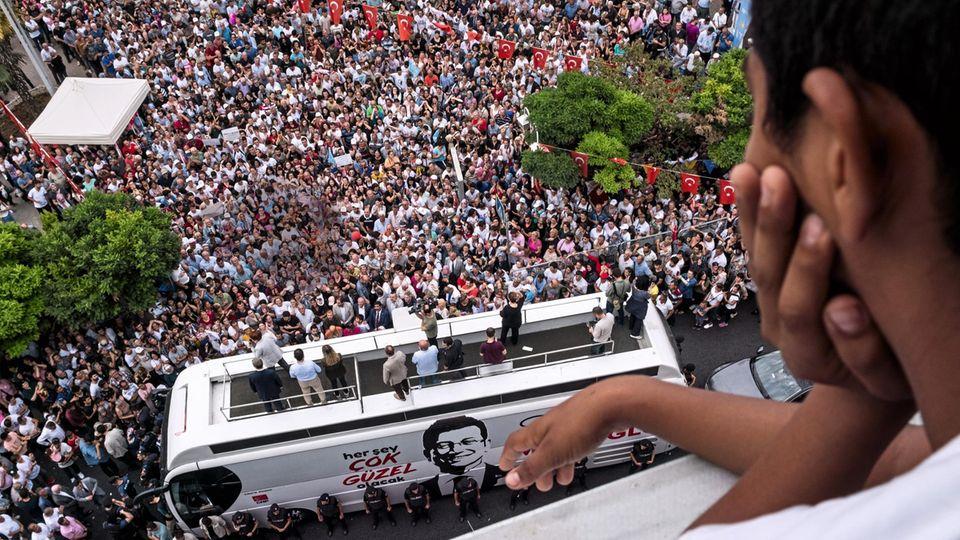 Wo sein Bus steht, sammeln sich die Massen: Viele wollen Imamoglu berühren. Oder zumindest die Windschutzscheibe. Polizisten sorgen für Ordnung.