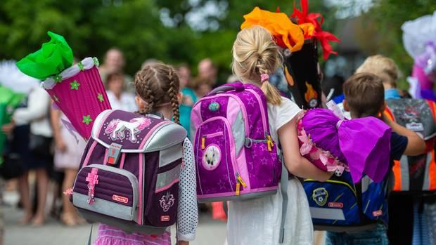 2 Mädchen und ein Junge sind von hinten zu sehen. Sie tragen Ranzen und Schultüten.