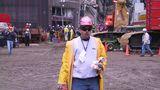 Ein Arbeiter mit Helm und gelber Regenjacke