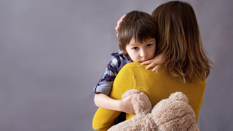 Eine Frau umarmt einen Jungen, der einen Teddybär hält