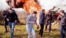Jugendliche rennen vor einem großen Feuer davon