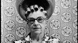 Eine alte Frau mit Brille sitzt unter einer Trockenhaube