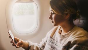 Frau mit Handy in Flugzeug