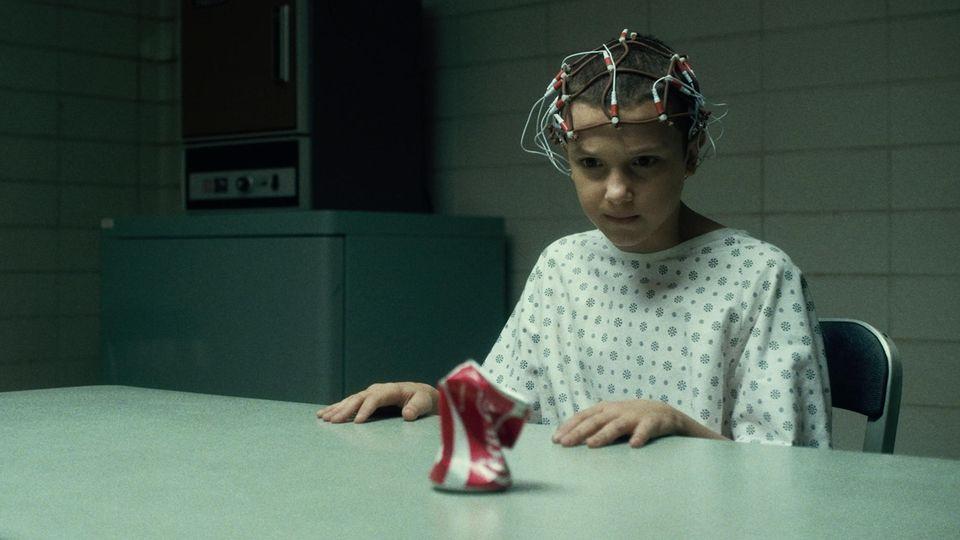 """Elfie aus """"Stranger Things"""" sitzt an einem Tisch mit Elektroden am Kopf und zerquetscht mit ihren Gedanken eine Coca-Cola-Dose"""