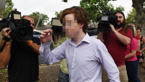 Ein junger Mann mit rotbraunem Seitenscheitel und im Karohemd geht an mehreren Kameraleuten vorbei