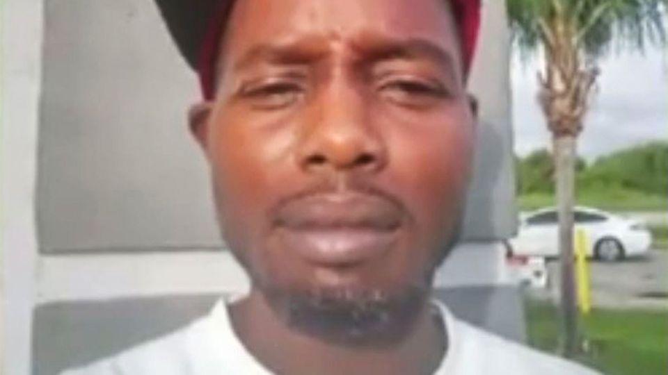 Ein farbiger Mann mit dünnem Oberlippen- und Kinnbart trägt ein weißes T-Shirt und ein Cap schräg auf dem Kopf