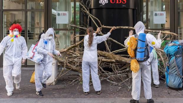 """Schweiz, Basel: Aktivisten der Gruppe """"Collective Climate Justice"""" blockieren mit Ästen den Eingang von dem UBS-Hauptsitz"""