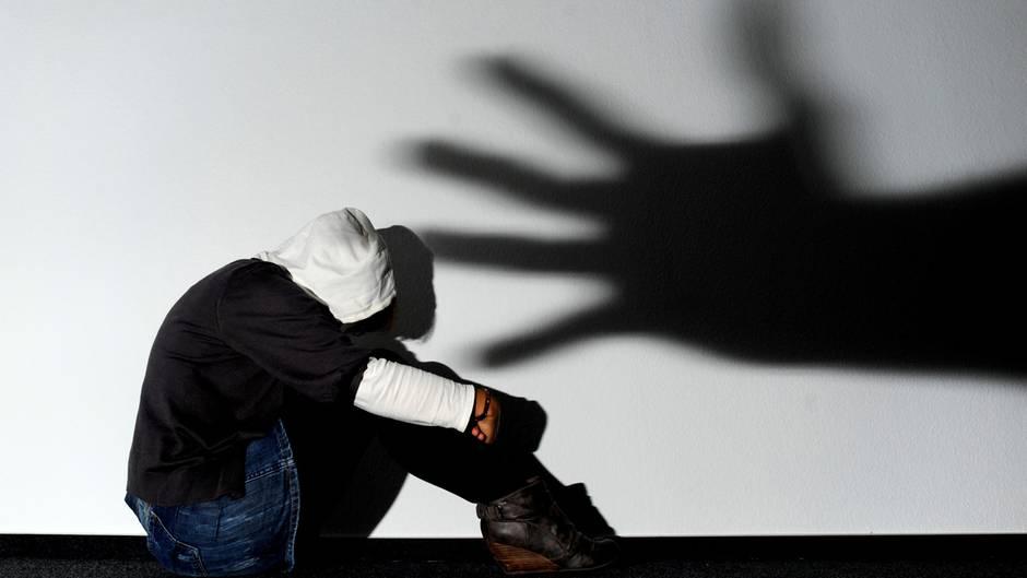 Der Schatten einer Hand über einer verängstigten jungen Frau