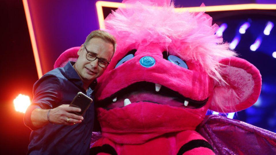 """Moderator Matthias Opdenhövel macht ein Selfie mit einem """"The Masked Singer""""-Showteilnehmer."""