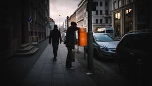 Ein Mann greift in einen Mülleimer und sucht nach einer Pfandflasche