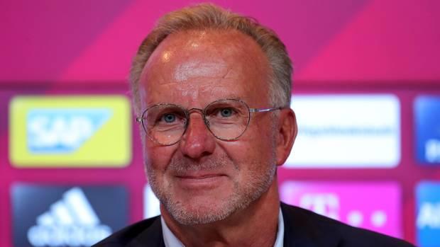 Karl-Heinz-Rummenigge, Vorstandsboss des FC Bayern München, sitzt in Hemd und Jackett vor einer Wand mit Sponsoren-Logos