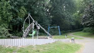Spielgeräte stehen vor Bäumen. Der Spielplatz ist mit Betonpollern abgegrenzt. Ein Sandweg führt über eine Wiese daran vorbei