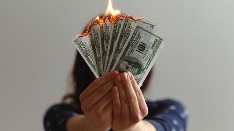 Frau mit brennenden Geldscheinen