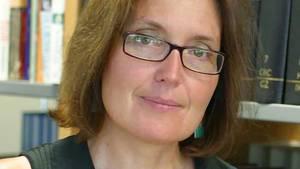 Eine Frau mit schmaler Brille und schulterlangen Haaren steht mit nach links geneigtem Kopf vor einem Bücherregal