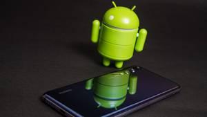 Das Android-Männchen steht neben einem Smartphone.