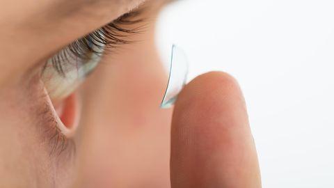 Ein Mann setzt sich mit einem Finger eine Kontaktlinse ein