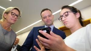 Jens Spahn schaut mit der sächsischen Sozialministerin Barbara Klepsch auf eine Klinik-App in Zwickau