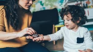 Homöopathie: Eine Frau gibt einem Jungen ein homöopathisches Mittel