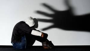 Ein Mädchen sitztvor einer Wand, auf der der Schatten einer Hand groß zu sehen ist