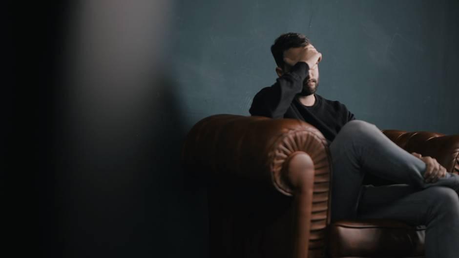 Mann sitzt auf einem Sessel und hat eine Hand über das Gesicht.