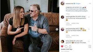 Vanessa Mai sitzt neben Axel Prahl auf einer Couch.