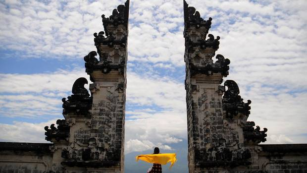 Eine Frau mit einem gelben Tuch steht zwischen den Säulen des Tempels