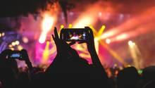 Konzertbesucher machen Fotos mit dem Smartphone