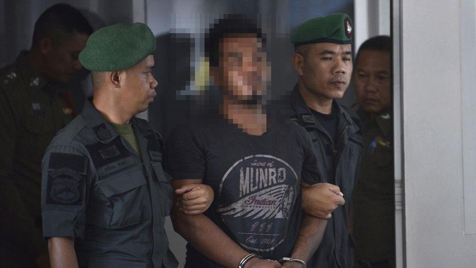 Polizisten führen den Mörder der deutschen Touristin in Handschellen ab