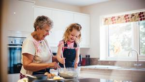 Ein Mädchen mit blonden Locken und ihre Großmutter machen einen Kuchenteig