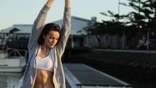 Eine trainierte Frau ist von vorne zu sehen und streckt ihre Arme nach oben.