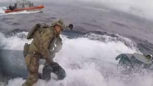 Die Männer der Küstenwache riskieren einen waghalsigen Sprung auf das mit hoher Geschwindigkeit fortfahrende Schiff.