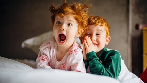 Zwei rothaarige Kinder im Bett