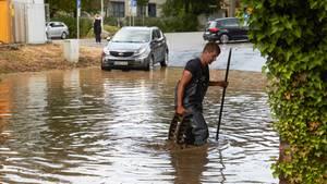 Ein Feuerwehrmann sucht nach einem Starkregen nach dem Ablauf