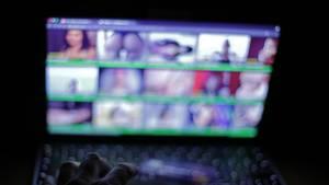 Ein Laptop-Bildschirm im Dunkeln zeigt eine Porno-Webseite