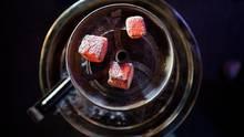 Glühende Kohle liegt auf einem Metallsieb über dem Tabak im Kopf einer Wasserpfeife in einer Shisha-Bar