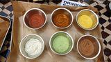 """Sechs verschiedene Saucen gibt's bei """"K.W.A."""". Oben von links:eine klassische Tomatensauce, Aci ezme, einetürkische scharfe Sauce undMango-Sauce. Und unten (von links): eineArt Tzaziki, eine Kräuter-Sauce mit Minze undMole, eine pikante Schokosauce."""