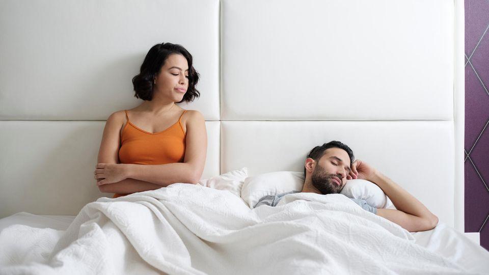 Frau guckt schlafenden Mann an