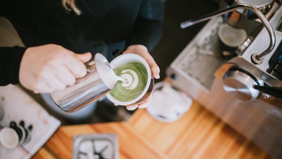 Frau grießt Milch in eine Tee-Tasse