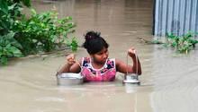 Ein Mädchen trägt Gefäße mit Trinkwasser durch überflutete Straßen in Indien