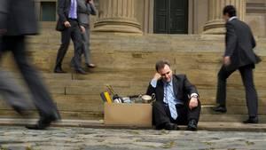 Ein Mann sitzt mit einem Pappkarton auf Stufen