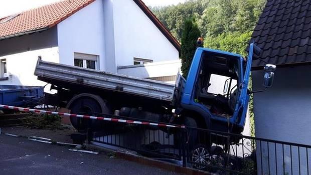 Der Lkw steht nach dem Unfall an einer Hauswand