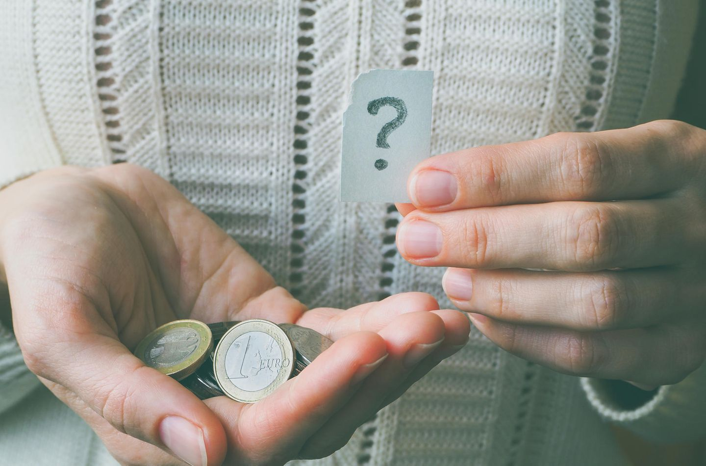 Frau hat Münzen in der Hand mit Fragezeichensymbol