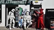 Science Fiction Figuren und ein kleiner Junge vor einem Supermarkt